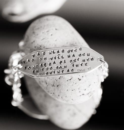 silverarmband med text på vit sten som ligger på en spegell