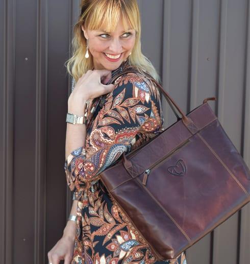 kvinna med brun skinnväska på axeln utomhus