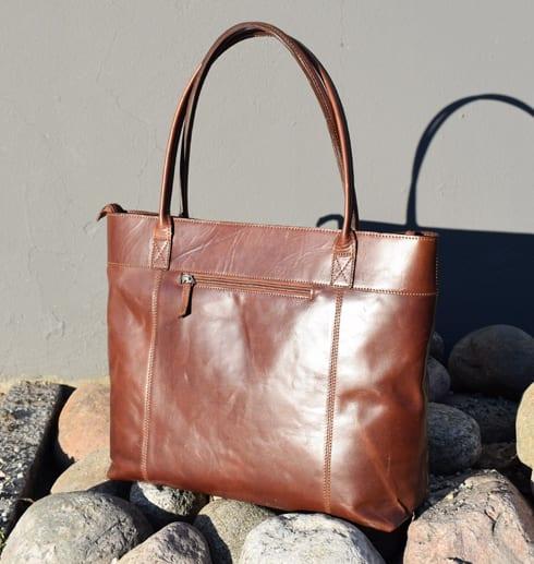 brun skinnväska på stenar mot grå vägg utomhus
