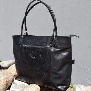 svart skinnväska på stenar utomhus