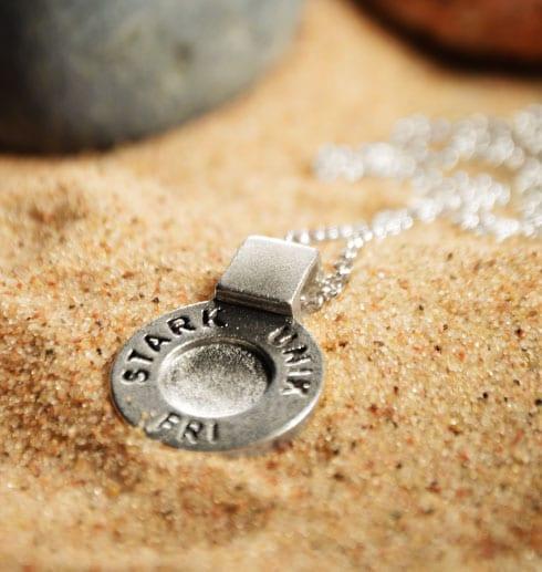 runt silversmycke i kedja med texten STARK, UNIK, FRI på beige sand