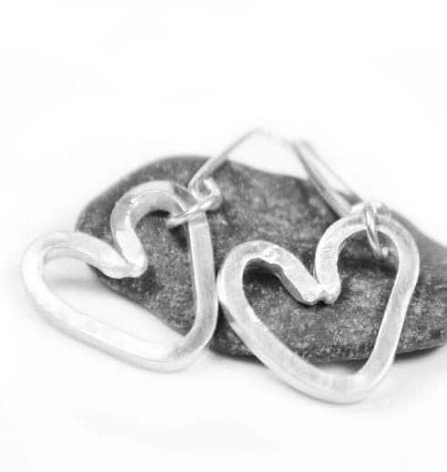 örhängen i silvertråd i form av hjärtan på grå sten