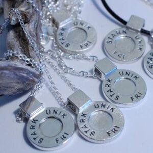 många runda silversmycken i kedja med texten STARK, UNIK, FRI på vit bakgrund med trädgren bredvid