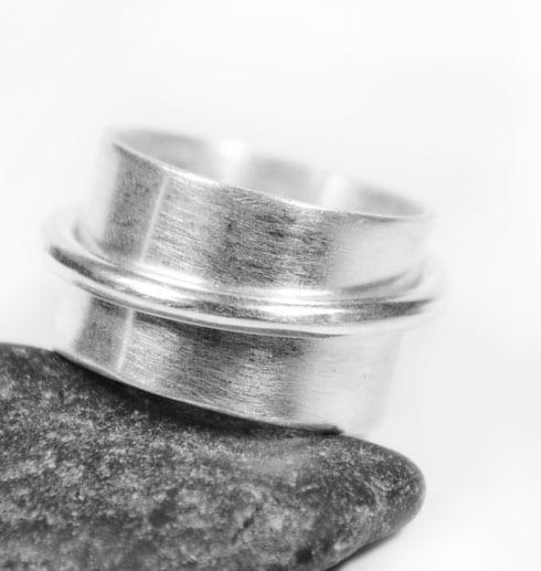 bred silverring på grå sten med vit bakgrund