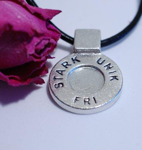 runt silversmycke i läderrem med texten STARK, UNIK, FRI på vit bakgrund med rosa ros bredvid