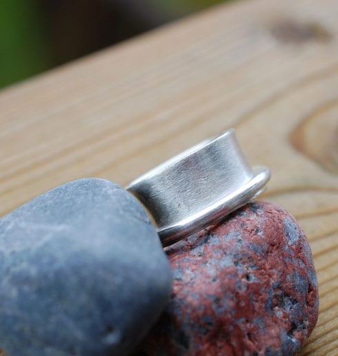 bred silverring på stenar utomhus