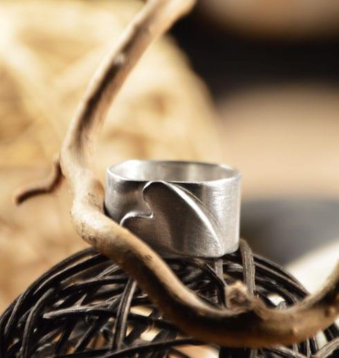 silverring med liggande hjärta liggande på en trådboll med trädgren bredvid