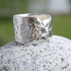 hamrad silverring med stenar på sten utomhus