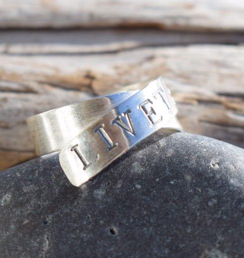 silverring med text på sten med trä bakom utomhus