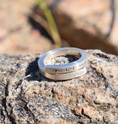 silverring med text på sten utomhus