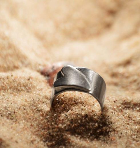 silverring med liggande hjärta nergrävd i sand