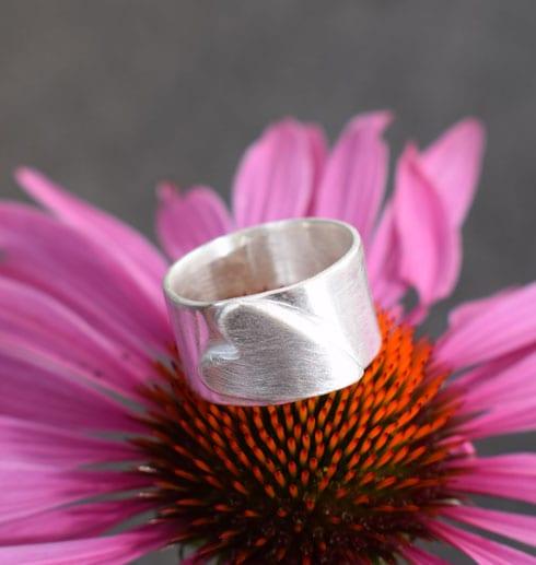 silverring med liggande hjärta i mitten av en rosa blomma
