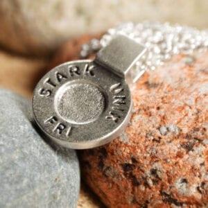 runt silversmycke i kedja med texten STARK, UNIK, FRI liggande på stenar en grå och en röd
