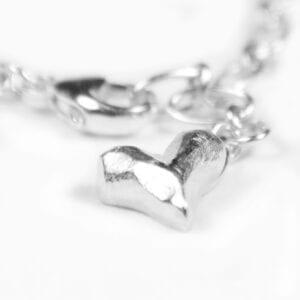 silverarmband med litet hjärta på vit bakgrund