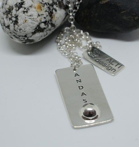 silversmycke med texten ANDAS på vit botten med stenar bakom