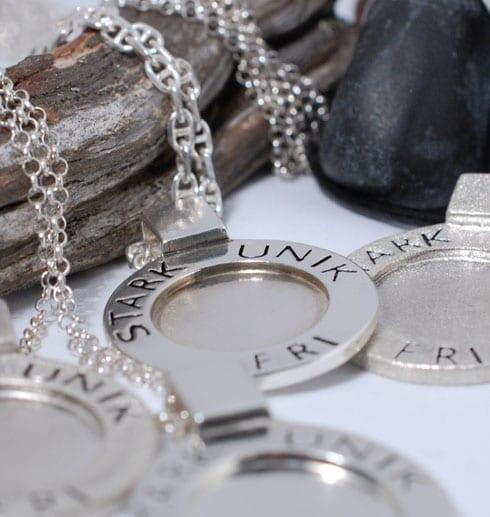 fyra silvershalsband med texten STRAK, UNIK, FRI liggande över trädgren och stenar