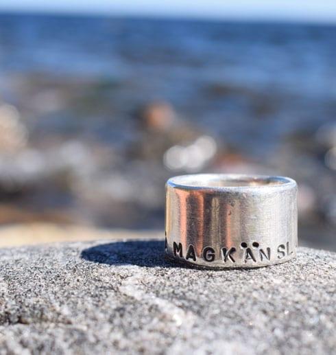 bred silverring med text på en klippa vid havet