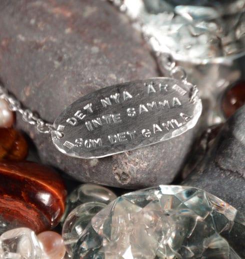 ovalt silverarmband med text på stenar