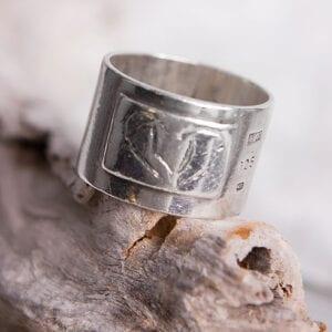 bred silverring på trädgren