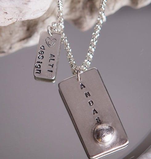silversmycke med texten ANDAS på spegel med trädgren bakom