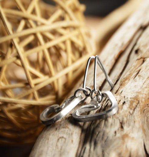 hjärtörhängen i silver på trädgren med trådboll bredvid