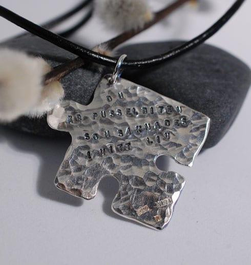 pusselbit i silver med text som hänger i en läderrem mot stenar