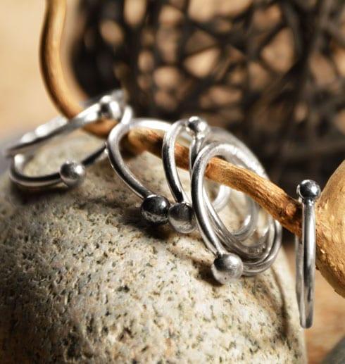 många smala silverringar på trädgren med sten under