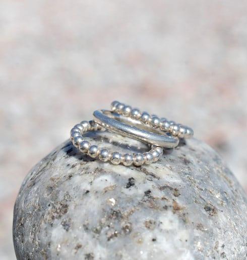 tre silverringar på sten utomhus