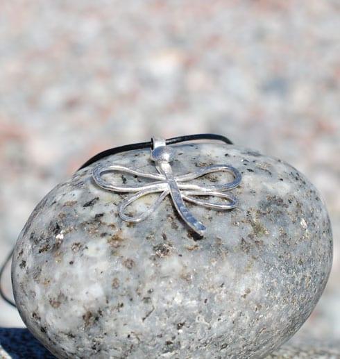 trollslända i silver på sten utomhus