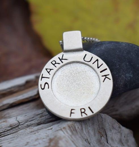 silverhalsband med texten STRAK, UNIK, FRI med träbit och stenar och gult löv