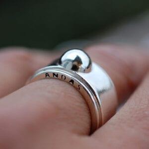 bred silverring med texten ANDAS på kanten på finger utomhus