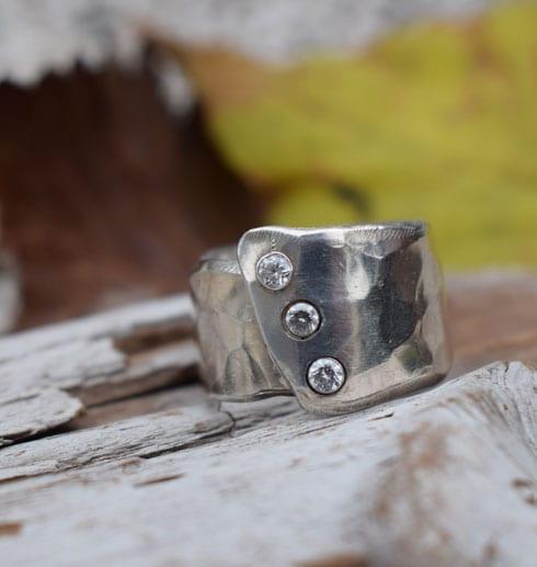 silverring med stenar på trä med löv bakom