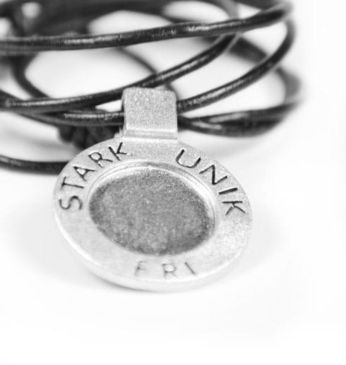 runt silversmycke i läderrem med texten STARK, UNIK, FRI på vit bakgrund