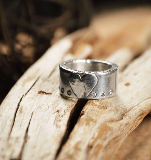 silverring med hjärta, stenar och text på trä