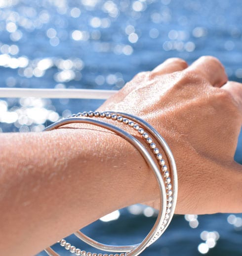 tre silverarmband på handled vid havet