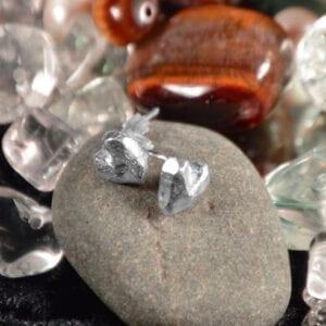 hjärtörhängen på sten med glasbitar bakom