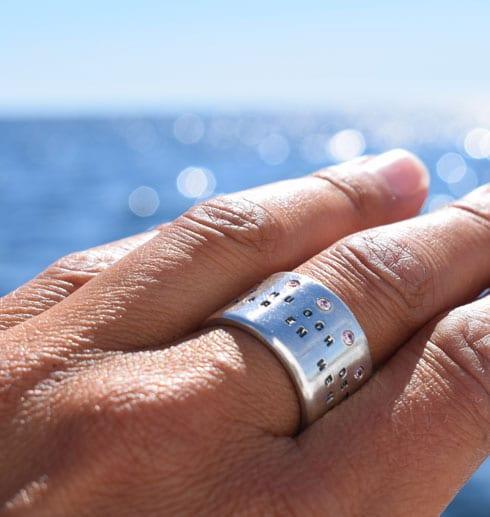 bred silverring med text och stenar på finger utomhus med havet som bakgrund