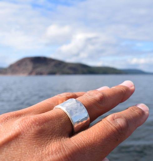 breda hamrad silverring på finger utomhus med hav bakom