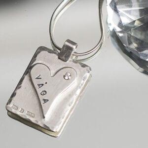 silverhalsband med hjärta och texct på spegel med diamant bredvid