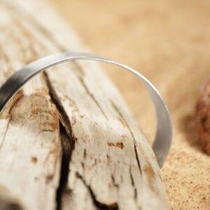 brett silverarmband på trädgren med sand bakom
