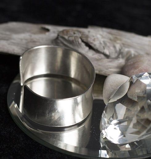brett silverarmband på spegel med trädgren och diamant bakom