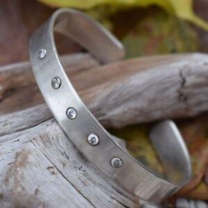 silverarmband med stenar på trädgren utomhus