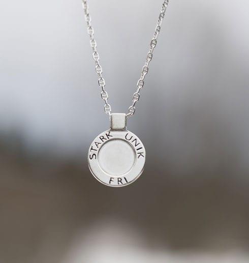 runt silversmycke med texten STARK, UNIK, FRI hängande i luften utomhus