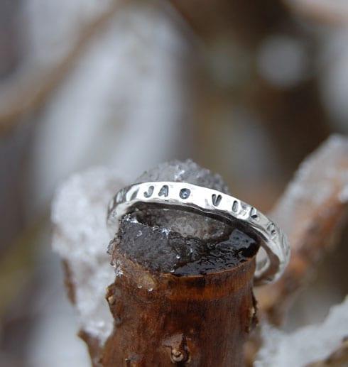 silverring med text på träpinne utomhus