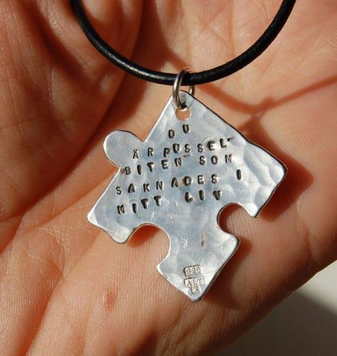 pusselbit i silver med text som hänger i en läderrem mot handflata