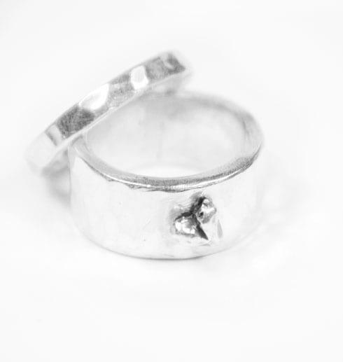 två silverringar med hjärta på vit botten