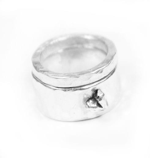 två silverringar med hjärta på vit bakgrund