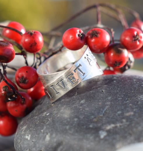 silverring med text på grå stenar med rönnbär bakom utomhus