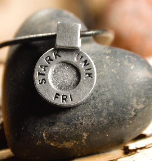 runt silversmycke i läderrem med texten STARK, UNIK, FRI på svart stenhjärta