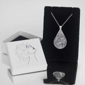 droppformat silversmycke med kvinnoansikte på svart sammetshållare med spegel och vit ask bredvid